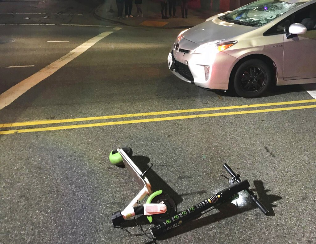 a broken scooter on the ground in front of a damaged car